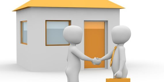 Individuals shaking hands in front of house